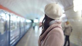 La mujer hermosa en una capa adentro metropiliten aguardando un tren almacen de metraje de vídeo