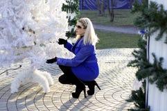 La mujer hermosa en una capa azul se sentó en un árbol del Año Nuevo Foto de archivo
