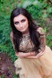 La mujer hermosa en vestido del oro es sonriente y de abrazo Imagen de archivo