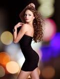 La mujer hermosa en vestido negro presenta sobre luces de la noche Fotos de archivo