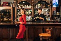 La mujer hermosa en vestido rojo coloca cerca de la barra un cóctel Fotos de archivo libres de regalías