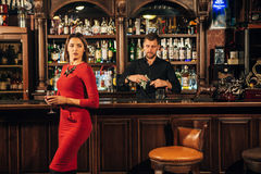 La mujer hermosa en vestido rojo coloca cerca de la barra un cóctel Imágenes de archivo libres de regalías