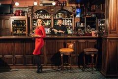 La mujer hermosa en vestido rojo coloca cerca de la barra un cóctel Foto de archivo
