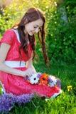 La mujer hermosa en vestido rojo hace una guirnalda de flores Imagen de archivo libre de regalías