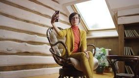 La mujer hermosa en vidrios toma la foto de sí misma en smartphone en ático metrajes