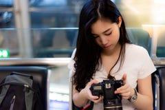 La mujer hermosa encantadora comprueba su cámara y fotos para saber si hay traveli imagen de archivo
