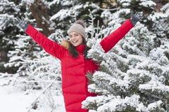 La mujer hermosa es feliz mientras que está nevando en el parque Foto de archivo