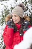 La mujer hermosa es feliz mientras que está nevando en el parque Fotografía de archivo