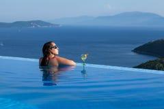 La mujer hermosa es relajante en una piscina del infinito Imagen de archivo libre de regalías