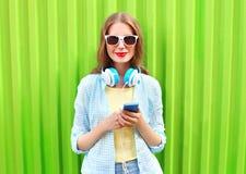 La mujer hermosa escucha la música en auriculares usando smartphone sobre verde Imagen de archivo libre de regalías