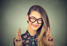 La mujer hermosa esperanzada que cruzaba sus fingeres, ojos se cerró, esperando, pidiendo mejor Imagen de archivo libre de regalías