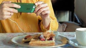 La mujer hermosa está comiendo las galletas en aplicaciones del café un smartphone de tomar una foto metrajes