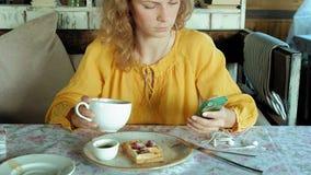 La mujer hermosa está comiendo las galletas en aplicaciones del café un smartphone de tomar una foto almacen de video