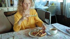 La mujer hermosa está comiendo las galletas en aplicaciones del café un smartphone de tomar una foto almacen de metraje de vídeo