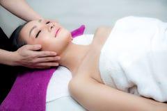 La mujer hermosa está consiguiendo un masaje facial en el salón del balneario fotografía de archivo libre de regalías