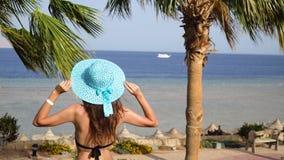 La mujer hermosa está descansando sobre la playa y está mirando el mar La muchacha endereza sombrero y establece abajo metrajes