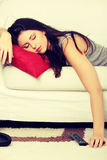 La mujer hermosa está durmiendo en la almohada roja. Fotografía de archivo