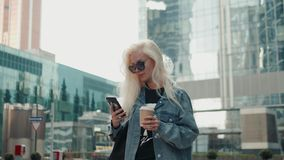 La mujer hermosa está enviando un mensaje de texto usando un app en su smartphone mientras que camina en el blonde del modelo de  metrajes
