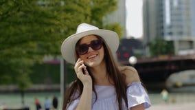 La mujer hermosa está hablando en exterior derecho del teléfono móvil en el muelle almacen de video