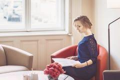 La mujer hermosa está leyendo la revista en casa Fotografía de archivo