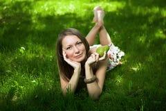 La mujer hermosa está mintiendo en la hierba foto de archivo