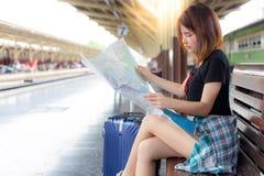 La mujer hermosa está mirando el mapa para planear su destino Pre foto de archivo