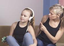 La mujer hermosa está regañando a su hija adolescente, la muchacha está escuchando la música en auriculares y está ignorando a su Fotos de archivo