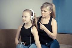 La mujer hermosa está regañando a su hija adolescente, la muchacha está escuchando la música en auriculares y está ignorando a su Fotografía de archivo libre de regalías