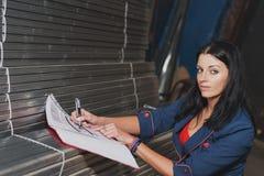 La mujer hermosa está registrando y está considerando de perfiles del metal adentro Foto de archivo