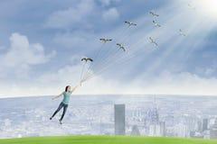 La mujer hermosa está volando sosteniendo pájaros Imagenes de archivo
