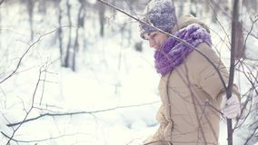 La mujer hermosa feliz está caminando en el bosque del invierno durante las nevadas metrajes