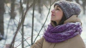 La mujer hermosa feliz está caminando en el bosque del invierno durante las nevadas almacen de metraje de vídeo