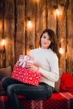 La mujer hermosa feliz joven con las cajas de regalo se sienta cerca de la pared adornada para la Navidad en el cuarto de la casa Fotos de archivo