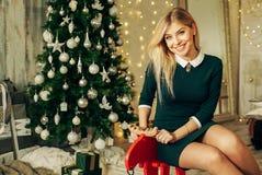 La mujer hermosa feliz joven con las cajas de regalo se sienta cerca del árbol de navidad en el cuarto de la casa Foto de archivo