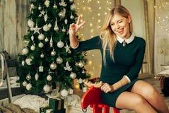 La mujer hermosa feliz joven con las cajas de regalo se sienta cerca del árbol de navidad en el cuarto de la casa Fotos de archivo libres de regalías