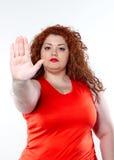 La mujer hermosa gorda en gesticular rojo con sus manos Foto de archivo libre de regalías