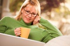 La mujer hermosa goza de su bebida y computadora portátil calientes Imagen de archivo