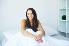 La mujer hermosa ha despertado y se está sentando en una cama blanca imagen de archivo