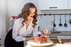 La mujer hermosa ha hecho la torta en cocina Fotos de archivo libres de regalías