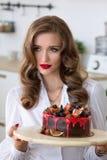 La mujer hermosa ha hecho la torta en cocina Foto de archivo libre de regalías