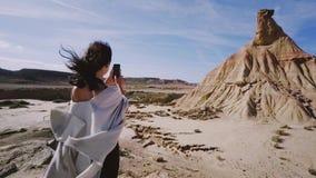 La mujer hermosa hace las fotos en el teléfono en desierto metrajes
