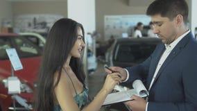 La mujer hermosa hace un trato acertado del coche de compra en concesión de coche metrajes