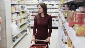 La mujer hermosa hacer las compras en el supermercado, steadicam tiró almacen de video