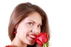 La mujer hermosa huele la rosa del rojo y mira la cámara Fotos de archivo