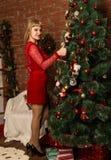 La mujer hermosa inred el vestido stending al lado del árbol de navidad y lo adorna fotografía de archivo