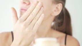 La mujer hermosa joven aplica la crema hidratante en cara almacen de metraje de vídeo