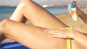 La mujer hermosa joven aplica la protección solar para los pies HD almacen de video