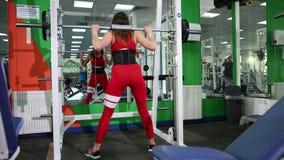 La mujer hermosa joven aumenta la barra en el gimnasio y toma el polo del metal alrededor de la cabeza metrajes