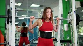 La mujer hermosa joven aumenta la barra en el gimnasio y toma el polo del metal alrededor de la cabeza almacen de metraje de vídeo