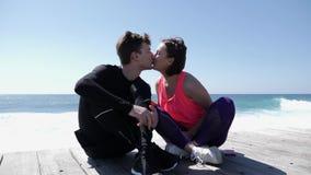La mujer hermosa joven besa al hombre juguetón apto en los labios cerca del océano C?mara lenta almacen de metraje de vídeo